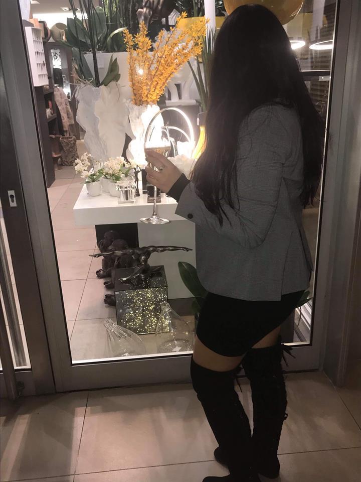 Fiorella Pauloz tenant une coupe de champagne devant une vitrine