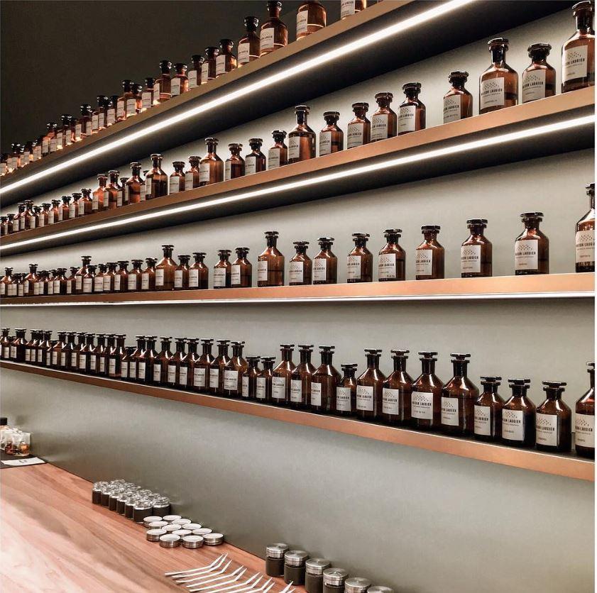Étagères avec les flacons vintages des différentes matières premières utilisées pour la création de parfum chez Maison Laugier.