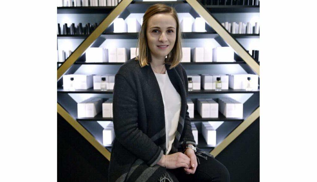 Elodie Campagne devant l'étagère de sa collection de parfum Maison Laugier.