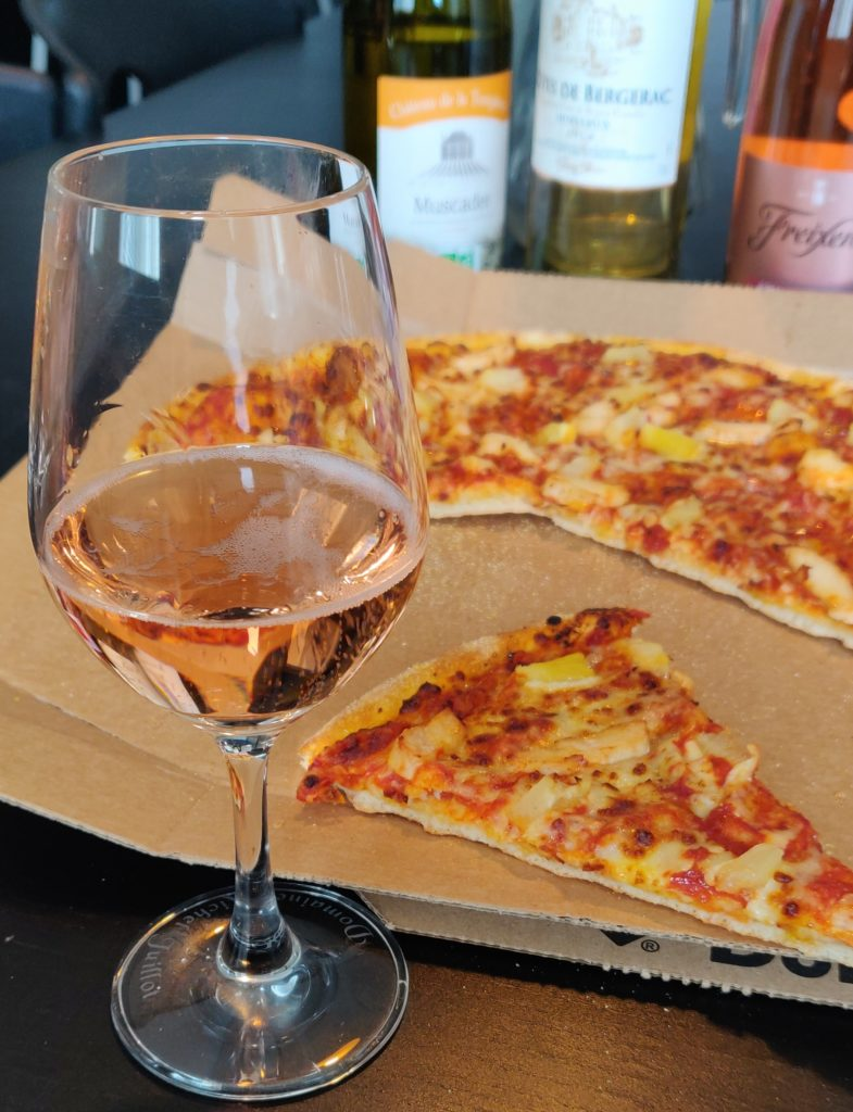 Photo d'une pizza hawaïenne avec un verre de Cava rosé effervescent