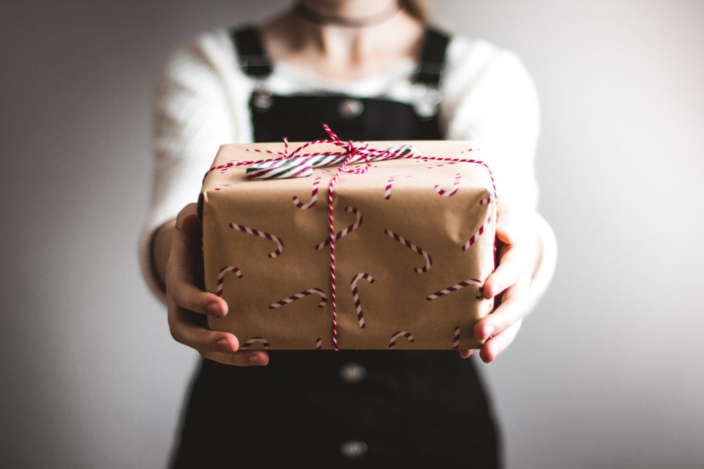 Femme tendant un cadeau de Noël
